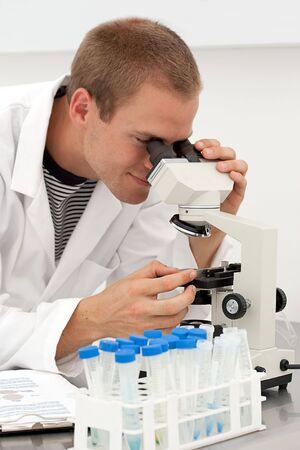 サンプルを顕微鏡で見ている若い男性ラボ技術者 写真素材