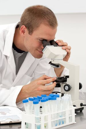 A young male lab technician looks at samples in a microscope photo