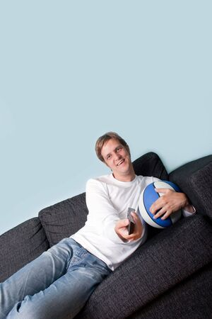 Happy young man holding tv remote and basket ball photo