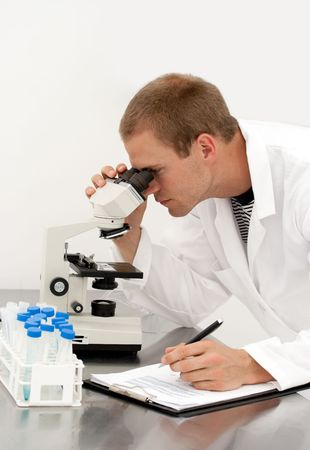 A young male lab technician looks through a microscope