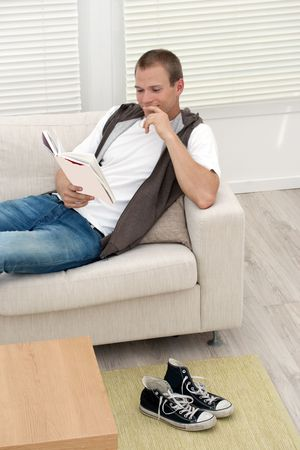 Smiling handsome young man relaxing and reading book