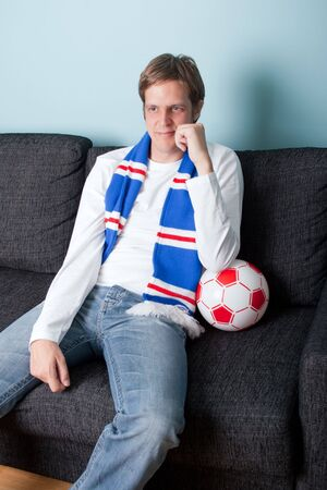 smiling young man supporting his football team on tv photo
