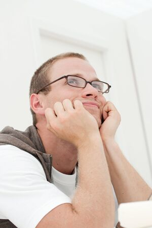 young handsome man daydreaming by the table Stock Photo
