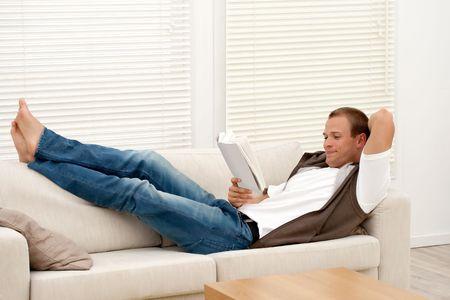 スマートの若い男はソファの上の本を読んで 写真素材