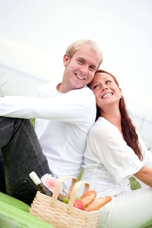 Couple on romantic picnic outdoors, looking cheerful