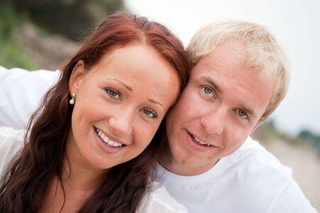 若いカップルの笑いとビーチで楽しんで
