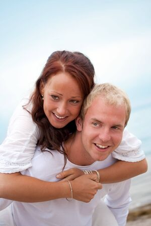 A young couple laughing and having fun on the beach photo