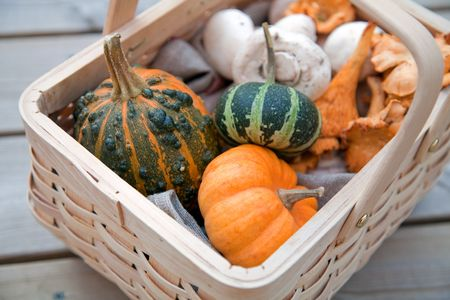 Wicker basket with pumpkins and mushrooms