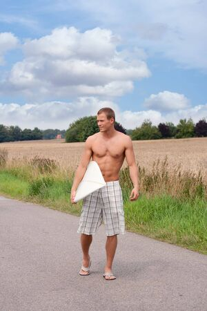 Surfer in checkered shorts on the way to the beach photo