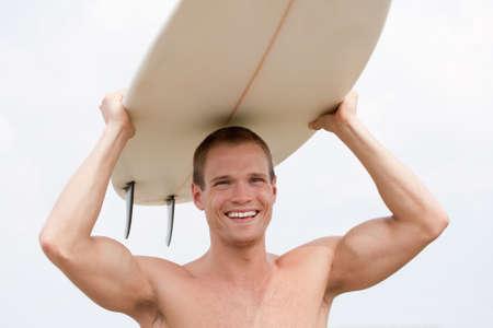 彼の頭にボードとホットのサーファー 写真素材