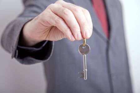 Landlord realtor holding out a key to your new home Stok Fotoğraf