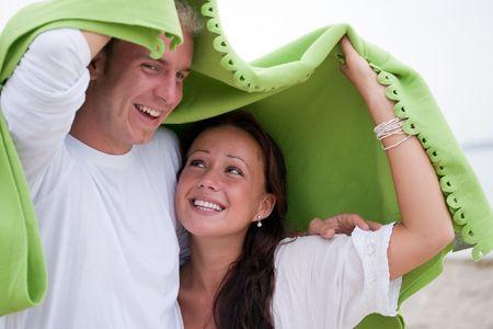 かわいいカップル毛布の下に避難。ビーチの設定
