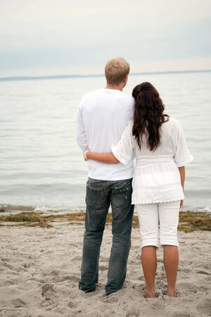 couple hugging standing by the shore photo