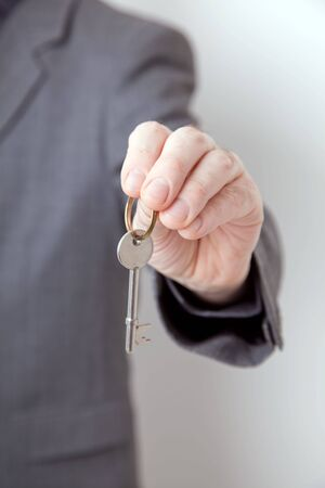 man holding out key - security, hotel or real estate concept
