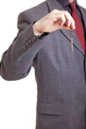 Landlord/ Hotel receptionist holding out a door key Stock Photo - 6168678