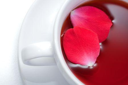 バラの花びらと赤いアフリカ ルイボス ティーお茶のカップ