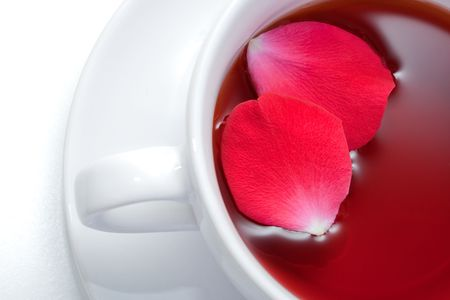 cup of african rooibos red tea with rose petals
