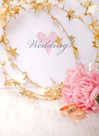 Wedding invitation with gold ribbon and rings photo