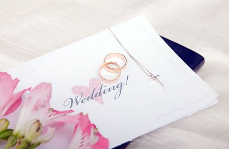 Pair of wedding rings on a bible with cross and flower photo