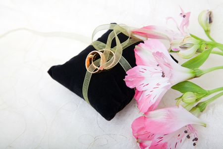 Wedding still life with rings, flowers and a felt cushion photo
