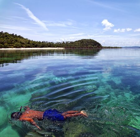 A young male snorkler swims at an island coral reef in Thailand.