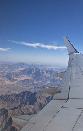 Image of an aeroplane going over mount sinai in the egyptian desert photo