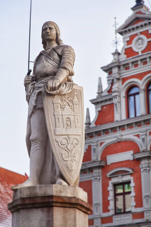 patron: Statue of patron saint Roland standing in Riga old town, Latvia  Behind is the famous Blackheads building