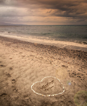 Image of a message of missing love written in sand on a stormy beach.  photo