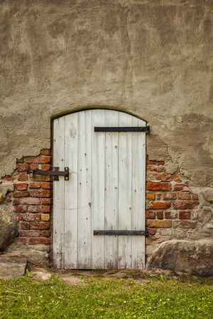 worn structure red: Image of an old white barn type door in a bricked building.