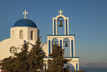 basking: Image of greek chapel basking in evening sunlight. Santorini, Greece. Stock Photo