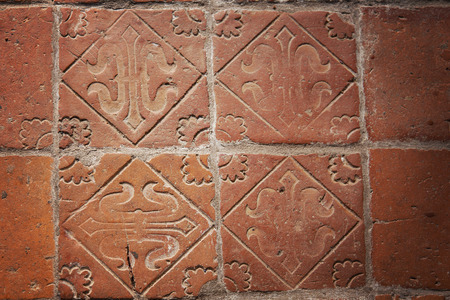 worn structure red: Image of medieval hand-made teracotta floor tiles.
