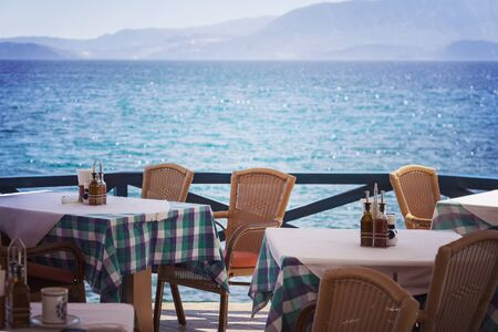 lunch table: Image of empty tables at seaside restaurant. Crete, Greece.