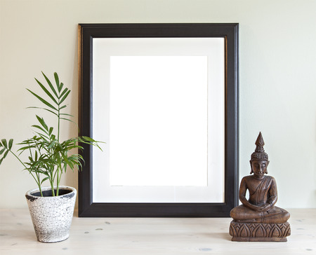 Image of a mockup scene with wooden frame, plant and buddha statue.