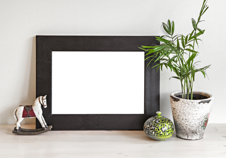 wall decoration: Image of a mockup scene with wooden frame, toy horse and plant pot.