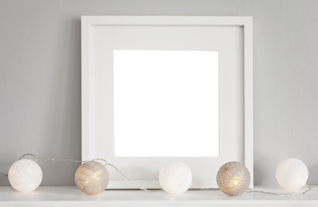 Image of a mockup scene with a white square frame and baubles. Banco de Imagens