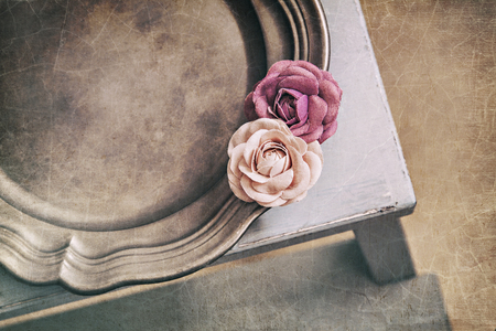 Image of vintage styled flat lay still life with fabric roses on tin platter.