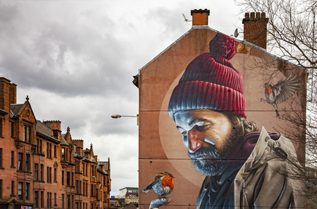 wall mural: GLASGOW APRIL 02, 2016; Mural painting of a man with birds, on wall in central Galsgow, Scotland. Editorial
