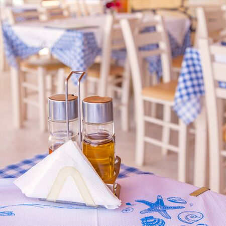 taverna: Detail image of a traditional greek taverna with condiments on the table.