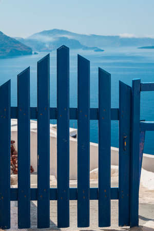 view of a wooden doorway: Image of a blue gate looking out over the caldera. Santorini, Greece. Stock Photo