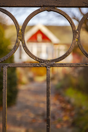 cottage fence: Image of metal fence by a cottage.