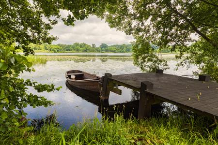 Image de lac avec un petit bateau en Suède rural. Banque d'images