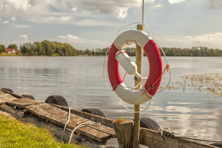 Image of life ring hanging by the lake shore. Stock Photo