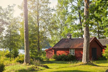 Image of picturesque red timber lake house. Smaland, Sweden.