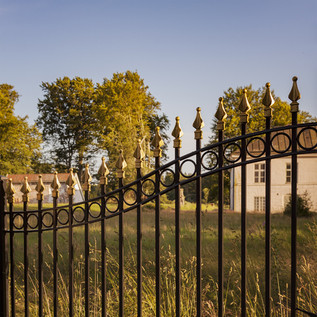 Image of decoatice cast iron fence by old farmstead.
