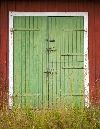 worn structure red: Image of green barn doors.