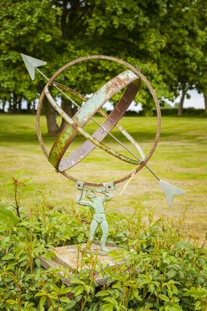 Vintage sundial in lush green garden. Stock Photo