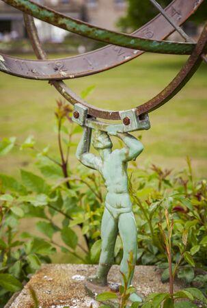 sun dial: Garden sun dial held up by bronze man.  Stock Photo
