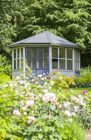 Image of lush garden with romantic gazebo.  Banco de Imagens