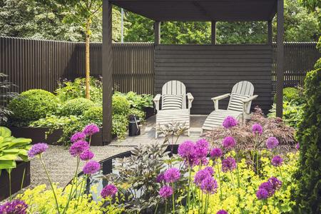 Gezellige lounge meubels op aangelegde tuin terras.