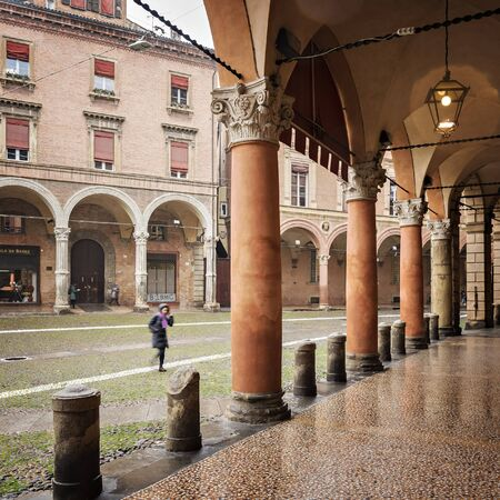 BOLOGNA, ITALY - FEBRURY 02, 2017. Porticos and people on a rainy Piazza Stefano.